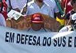"""Pessoa segurando cartaz, aparecendo escrito """"em defesa do SUS"""""""