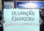 """Auditório em mesa da 15ª Conferência Nacional de Saúde,  com cartaz escrito """"Ocupação educadora"""""""