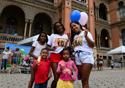 Duas mulheres e três crianças sorriem segurando balões coloridos diante do castelo mourisco