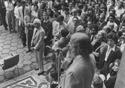 Homem fala ao microfone, cercado por dezenas de pessoas