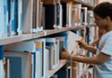 Imagem de criança pesquisando livro em estante de biblioteca