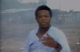 Ator negro fala para a câmera diante de cenário que reproduz favela, em imagens nitidamente antigas