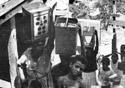 Foto antiga, em preto e branco, mostra mulheres carregando latões de água na cabeça e crianças olhando para a câmera