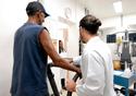 Homem, de costas, anda no que parece uma esteira ergométrica, supervisionado por um médico