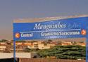 Vista aérea da favela com placa do trem, indicando o nome Manguinhos
