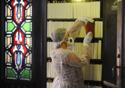 Mulher usando roupa especial tira um livro da prateleira; ao lado, porta com vitrais