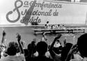 Foto em preto e branco mostra palco da Oitava Conferência, com mãos levantadas, em voto, vistas de costas