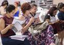 Pessoas lendo documento em auditório
