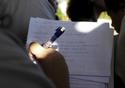 Recorte numa mão escrevendo a caneta num caderno