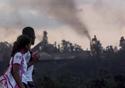 Duas meninas com uniforme de escola passam em frente a paisagem de onde fumaça exala