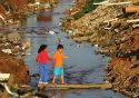 Duas crianças atravessando umaa ponte sob um canal de esgoto a céu aberto