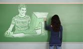 Menina desenha num quadro negro a imagem de um rapaz diante de um computador
