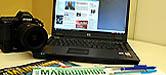 Foto composta com uma câmera fotográfica, um laptop e varias revistas.