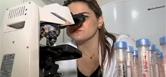Mulher pesquisando no microscópio