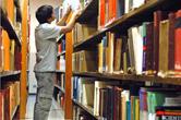 Homem pesquisando na biblioteca