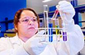 Imagem de uma mulher, observando tubos de ensaio