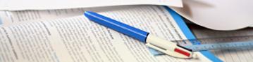 Uma caneta pousa sobre a página aberta de um livro