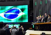 Fotografia do planério, no dia dahomanagem, com bandeira do Brasil no telão