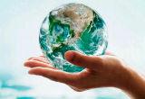 Mão segurando uma miniatura do planeta Terra