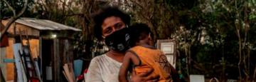 Mulher de máscara com criança no colo
