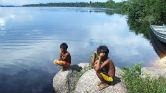 Meninos na beira de um rio