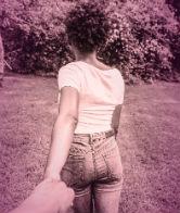 Foto envelhecida de moça de costas para a câmera de mãos dadas com alguém que não se vê