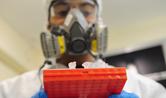 Profissional de máscara manuseia caixa com tubos de ensaio