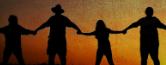 Silhuetas de pessoas de mãos dadas ao nascer do sol