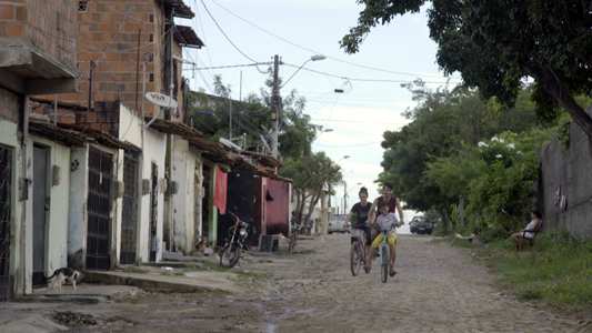Pessoas andando de bicicleta em uma rua de terra batida