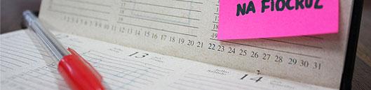 Foto de uma agenda aberta com caneta e post it