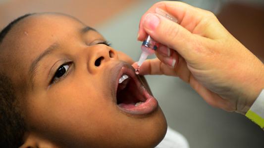 Criança tomando vacina em gotas