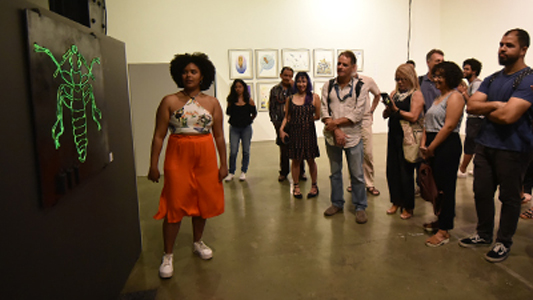 Pessoas observando a exposição