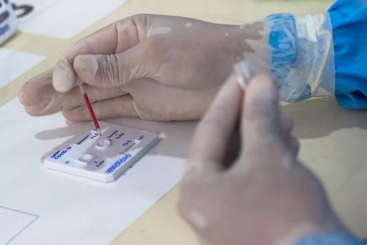 Mãos enluvadas realizam procedimento de teste em laboratório