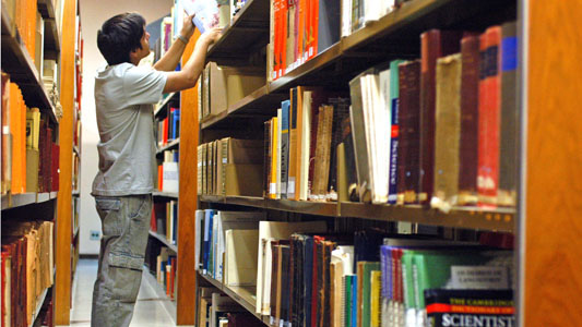 Young man looking for a book in a library