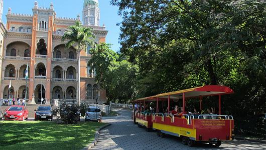 Foto mostra o trenzinho do museu, na frente do Castelo da Fiocruz