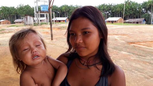 Menina com bebê no colo em aldeia indígena
