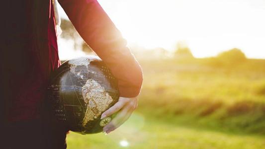 Mulher com um globo com o mapa do mundo em baixo do braço