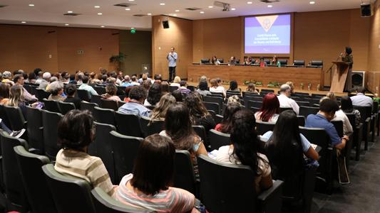 Foto geral do local do evento, apresentando plateia e participantes da mesa de abertura