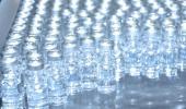 Foto de linha de produção com frascos de vacina