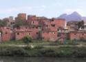 Favela com amontoado de casinhas de tijolos aparente, à beira de um rio